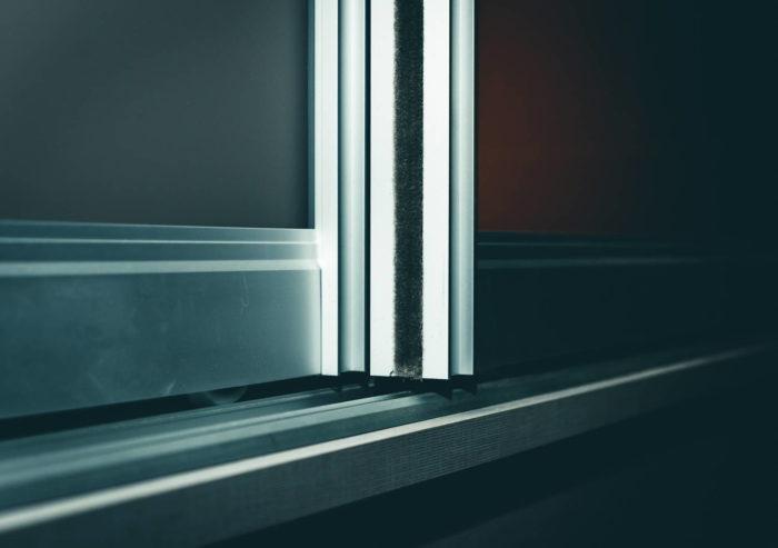 Diese Ansicht der Schiebetüren im geschlossenen Zustand lässt die vertikal angebrachte Filzkante erkennen, welche für ein leises und sanftes Öffnen sorgt. Ebenso zeigt sich hier die Profilkonstruktion mit Aluminium-Leichtlaufschiene mitsamt Leichtlauf-Rollen.