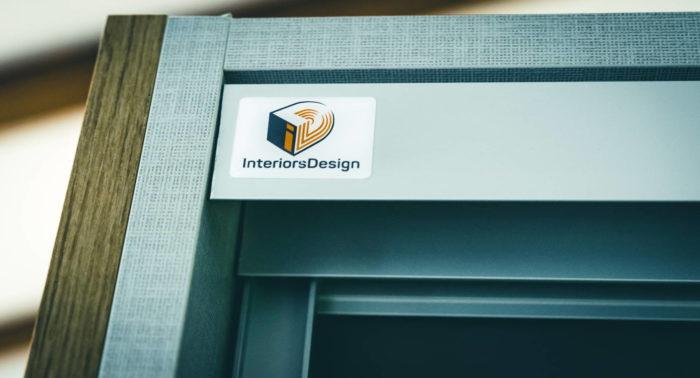 An der oberen linken Ecke zeigt sich der passgenaue Übergang der verwendeten Materialien Holz- und Leinendekor mit Oberflächenstruktur sowie die Schiebetürenkonstruktion aus Aluminium. Auf der Aluminiumblende der Schrankoberseite ist linksseitig ein kleines Interiors.Design Logo angebracht.