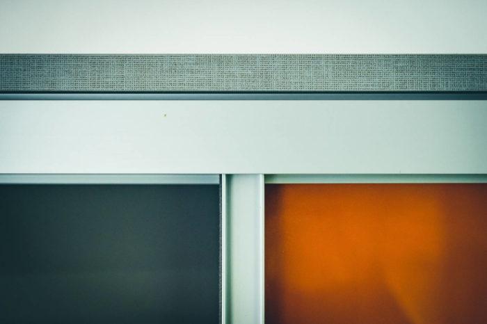 Hier bildlich festgehalten ist die Kombination der verschiedenen verwendeten Materialien: Leinendekor mit Oberflächenstruktur, Aluminiumprofile mit Leichtlaufschienen und das zweifarbige Schiebetürendekor mit antraziter und orangener Glasoberfläche. Ihrer Kreativität ist in der Oberflächenauswahl keine Grenze gesetzt.
