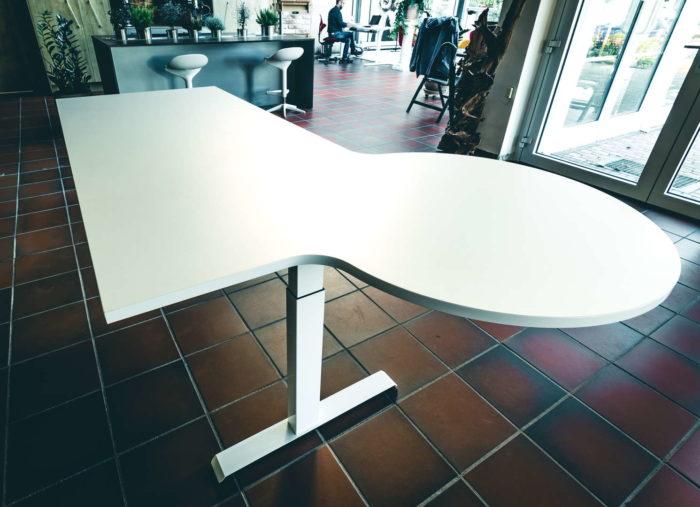 Draufsicht auf den Schreibtisch bei mittlerer Höheneinstellung. Die Form der Tischplatte ist selbstverständlich individuell. Hier ist die rechteckige Grundform mit weißer Oberfläche um einem kreisförmigen Ausleger erweitert. Ideal als Ablageort oder als kleiner Konferenztisch. Die Bedienung der Höhenverstellung erfolgt über das Bedienpanel an der dem Benutzer zugewandten Tischkante, oder per App.