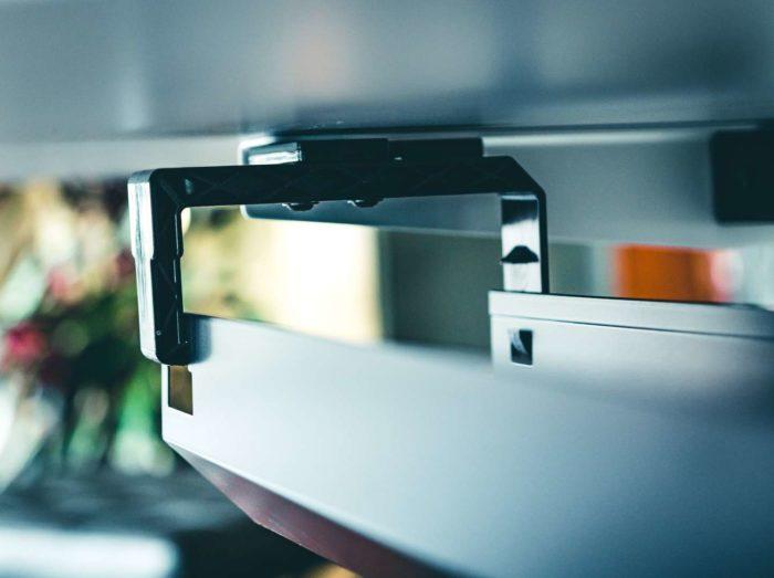 Stabile Rahmenkonstruktion an der Tischunterseite mit großer horizontal angebrachter und klappbarer Kabelwanne aus Stahl.