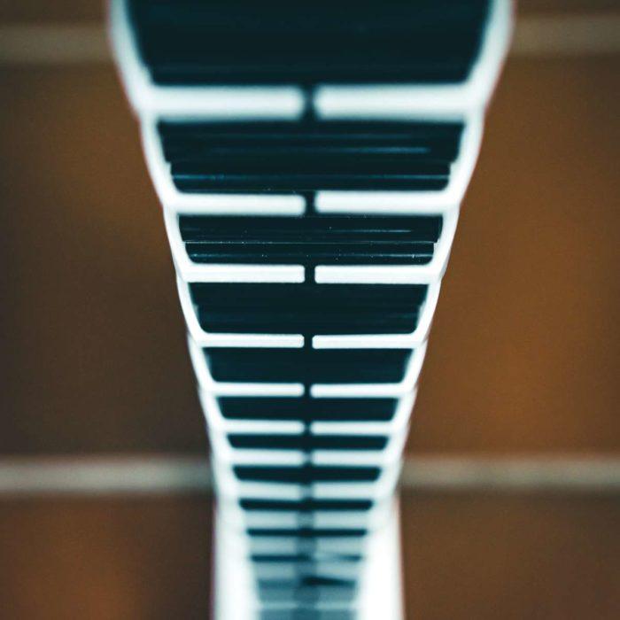 Frontal-Vogelperspektive der sich rückseitig am Tischbein entlang bewegenden Kabelspirale.