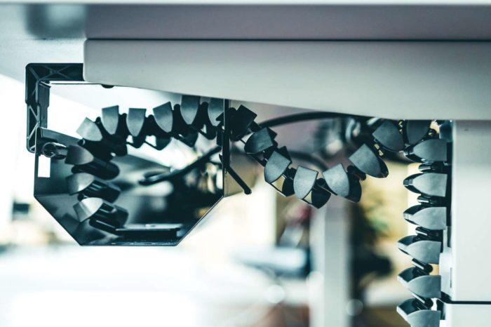 Die vertikale Kabelführung vom Boden zur Tischplatte bzw. in die Kabelwanne erfolgt mit einer Kabelspirale, die aus vielen gelenkigen Gliedern besteht. Durch die rückseitige Anbringung am Tischbein bleibt die Ordnung bei jeder Höheneinstellung gewährleistet. Die Bedienung der Höhenverstellung erfolgt über das Bedienpanel an der dem Benutzer zugewandten Tischkante, oder per App.