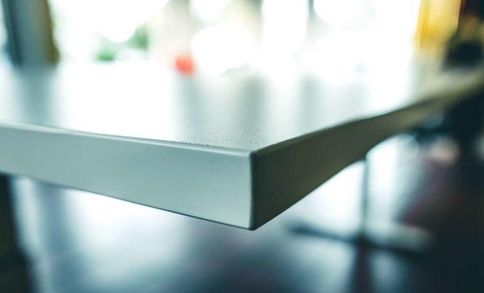 Nahaufnahme der Tischkante mit feuchtigkeitsabweisender und langlebiger Oberfläche in robuster Officequalität.