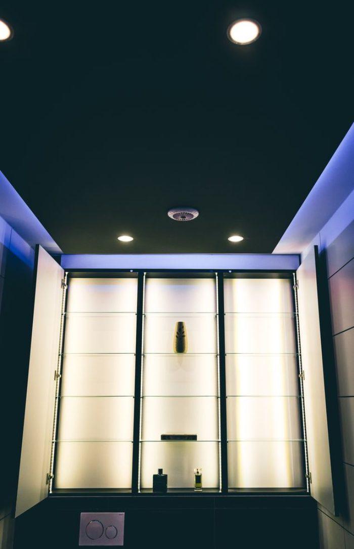 Mit aufgeklappten Türen links und rechts zeigt der Wandschrank was in ihm steckt – eine Menge Platz auf den gläsernen Ablagen und die vollflächig leuchtende Innenseite. Der Mittelteil hat keine Türen und eignet sich dank der Hintergrundbeleuchtung für eine effektvolle Dekoration. Die passgenauen Türen sind an der Front mit schwarzem glänzendem Glas versehen.