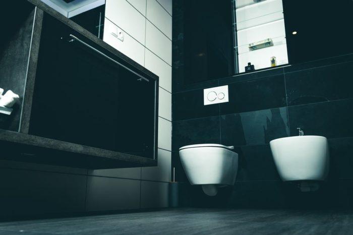 Schaffen Sie modulare Kontraste: Links vor hellem Fliesendekor der dunkle Waschtisch in Natursteinoptik und rechts vor schwarz glänzenden Oberflächen die hell beleuchtete Vitrine sowie die weiße Toilette und das Bidet.