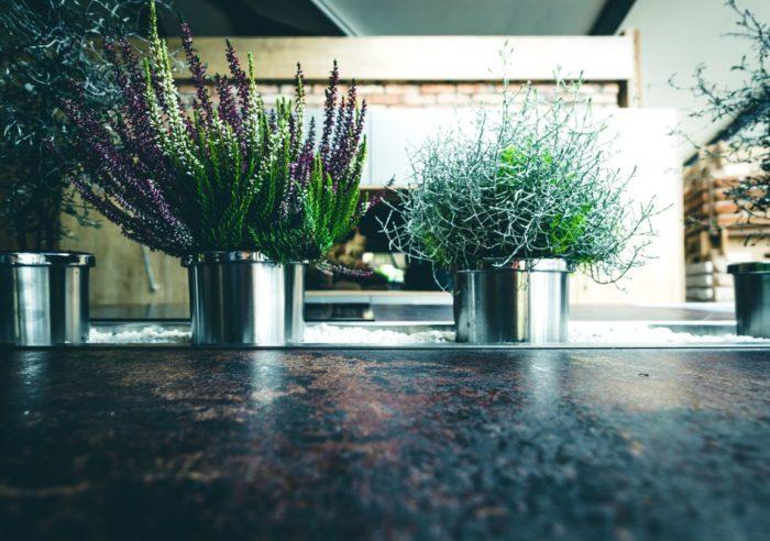 """Die motorisch ausfahrbare Mittelkonsole der Küche """"Venedig"""" lässt sich dekorativ mit Zimmerpflanzen oder Kräutern verschönern. Die Konsole ist passgenau in die robuste Arbeitsfläche in Rostoptik eingelassen."""