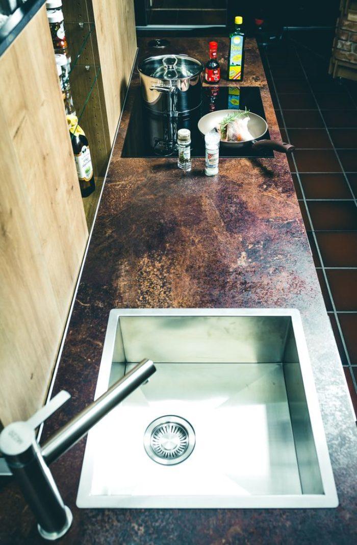 Edelstahlspülbecken, Armaturen und Ceran-Kochfeld sind passgenau in die Arbeitsfläche in Rostoptik eingelassen. Dank versiegelter Kanten ist die Oberfläche resistent gegen Feuchtigkeit. Bei ausgefahrener Mittelkonsole haben Sie Zugriff auf alles was Sie zu Kochen benötigen. Bei Nichtgebrauch verschwindet alles im Küchenblock und sorgt so im Nu für minimalistische Ordnung.